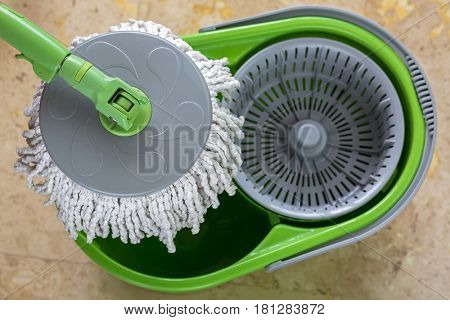 Used round spin mop with microfiber head, green handle on cleaning bucket with blurred yellow tiles floor