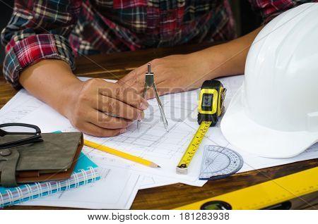 Engineering draftsman sitll working in the office.