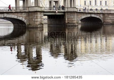 Lomonosov bridge reflected in the water of the river of Fontanka St. Petersburg on the bridge are people cloudy day