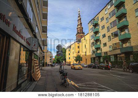 COPENHAGEN DENMARK - JUNE 15: Street in the city center of Copenhagen with he spire of the Church of Our Saviour in 2012