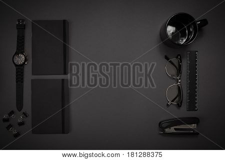 Black objects from the office on a dark gray background. Work and creativity. Social media concept hero header image. Top view. Still life. Copy space