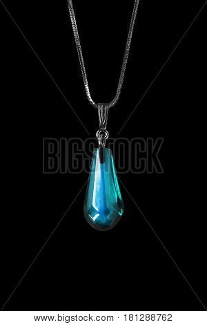 Blue topaz pendant on a chain on black background