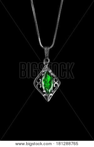 Vintage emerald pendant on a chain isolated over black