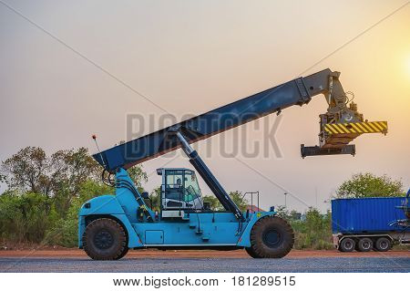 Cranes truck are lifting containers from trucks to freight by trainLogistics and transportation of container with working crane at sunset logistic import export and transport industry.