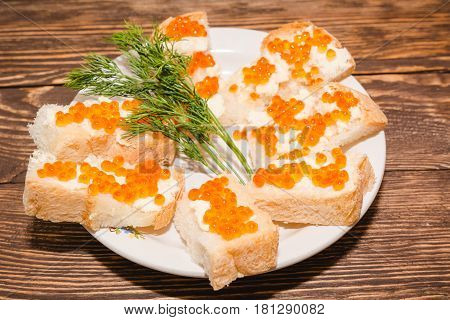 Red Caviar. Caviar On A Piece Of Bread And Butter. A Delicacy Caviar With Oil On A Table.