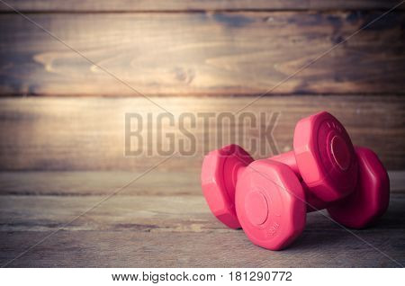 Double red dumbbells 1 kg on wood background.