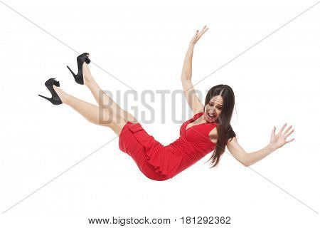 Side view of a scared female in red dress falling down. Young long-haired woman looking down while floating in the air