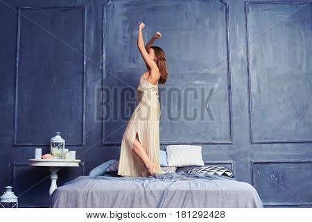 Side view shot of a young female dancing on the bed early in the morning. Good-looking brunette wearing long nightgown having fun after awakening