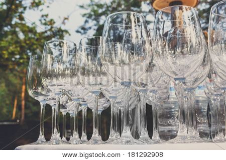 Catering background. Empty wine glasses at wedding restaurant reception outdoors. Shiny clear glasses in row