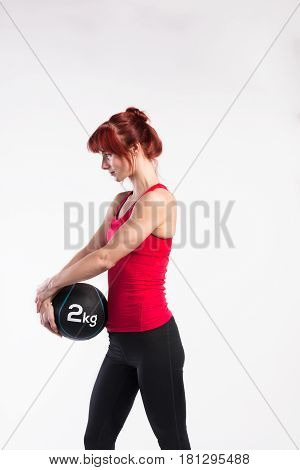 Attractive young fitness woman in red tank top, holding medicine ball. Studio shot on gray background.