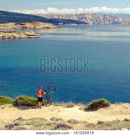 Mountain biker celebrating and looking at inspiring landscape riding a bike in summer mountains and sea. Man rider cycling MTB on country road or track. Sport fitness motivation and inspiration.