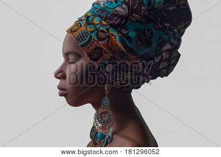 Young beautiful fashion model with traditional african style with scarf earrings and nude makeup isolated on gray background.