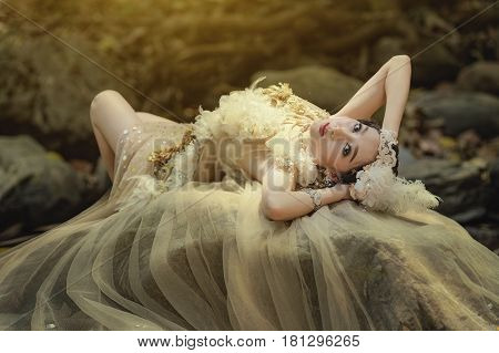 Fantastic womanbeautiful fantasy girl fairy in blowing transparent chiffon dress Fashion model lady in windy autumn parkYoung beautiful sexy women and makeup in fantasy.