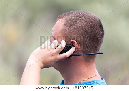 a man with a walkie-talkie outdoors . A photo