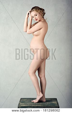 Closeup beautiful pregnant nude lady in elegant pose isolated on white background. Portrait of sexy fashion model girl indoors. Beauty sensual woman with attractive body. Close-up female naked belly