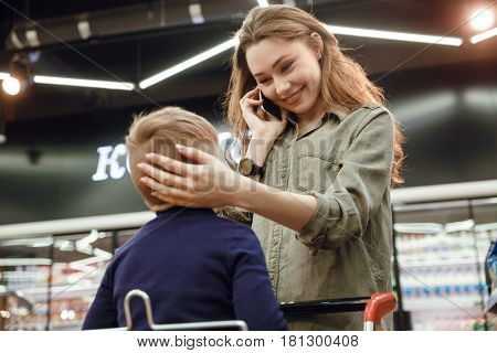 Young beautiful woman mother caressing her son's head while he sitting in cart in shopping centre