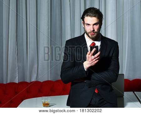 bearded man businessman long beard brutal caucasian hipster with moustache with glass of whiskey and cell phone has serious face unshaven guy with stylish hair in suit and red tie