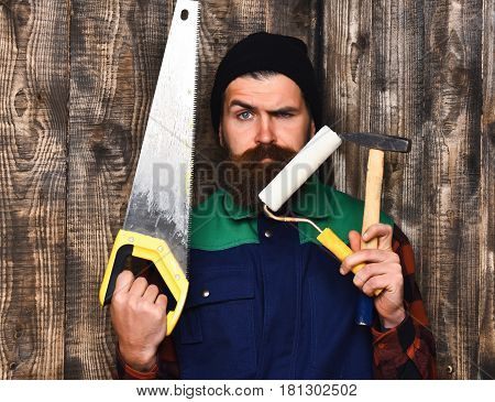 Bearded Man Holding Various Building Tools With Serious Face