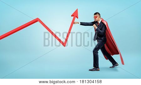 A businessman in a red superhero cape throwing punches at a red statistic arrow pointing upwards. Financial results. Fighting for success. Profit and investment.