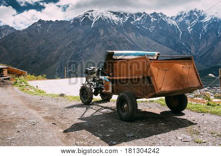 Stepantsminda Gergeti, Georgia. Small Old Two-wheel Tractor Or Walking Tractor French With Trailer Used In A Rural Household. Tractor On Road In Village On Mountain Background