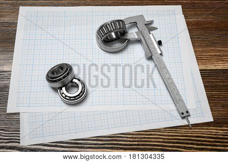 A large vernier scale lying on cross section paper with three bearings around it on wooden background. Engineering and repair. Workshop environment. Building tools and equipment.