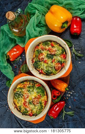 Frittata with broccoli spinach sweet peppers and tomatoes in two ceramic forms for baking. Italian omelet with vegetables. Top view