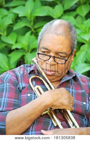 African american jazz musician with his trumpet outdoors.