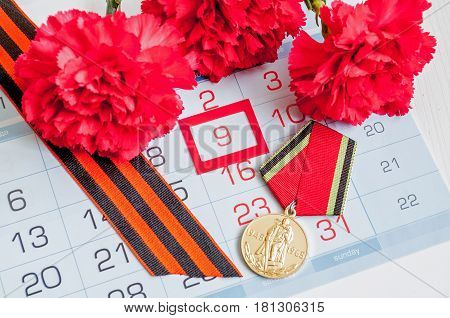 VELIKY NOVGOROD RUSSIA -CIRCA APRIL, 2017. 9 May - medal of victory in Great patriotic war with red carnation and George ribbon on the calendar with 9 May date. 9 may concept
