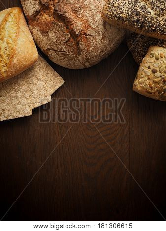 Tasty bread on a rustic wooden background with space for text view from above