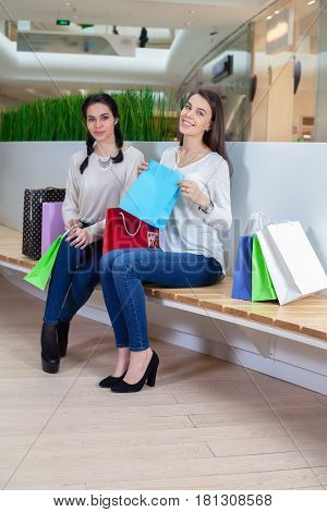 Two Cute Girls Are Sitting On A Bench In The Mall With Gift Bags .