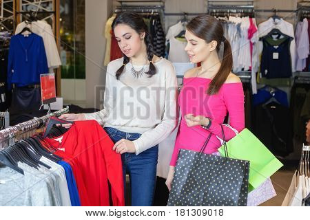Two Cute Girl Walks In The Mall With Gift Bags.