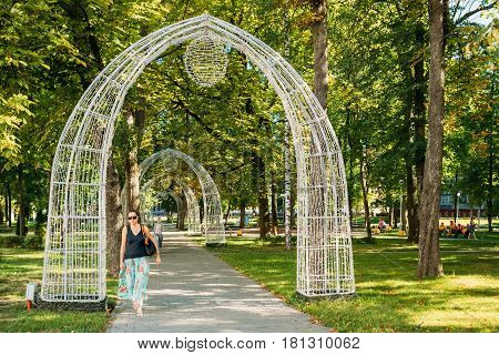Gomel, Belarus - August 10, 2016: Young Woman Passing Through Decorative Arches In The Pioneer Square On Sovetskaya Street In A Summer Sunny Day.