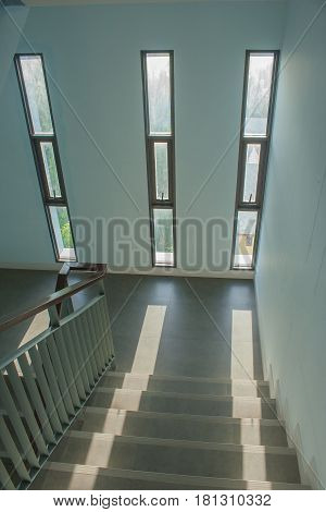 Staircase with a handrail in a buildings and sunlight through window background.
