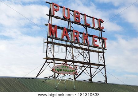 SEATTLE, WASHINGTON, USA - JAN 24th, 2017: Neon public market sign against cloudy sky, Pikes Place Market in downtown is a famous sight