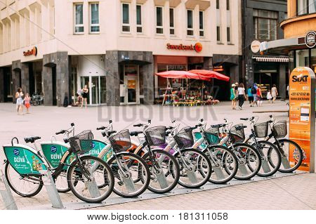 Riga, Latvia - July 2, 2016: Row Of Colorful Bicycles For Rent At Municipal Bike Parking In Kalku Street, Popular Showplace Of Old Town In Summer Day.