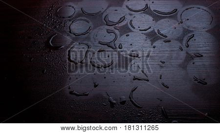 Empty wooden table with water drops against the background of autumn trees. The background is blurred. After the rain