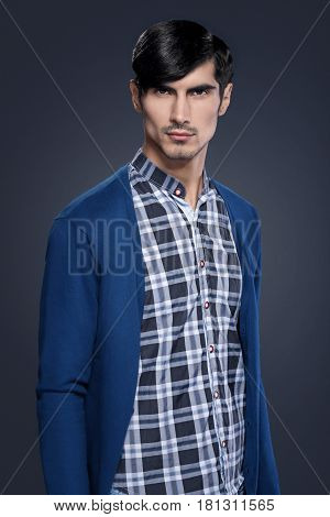 Handsome young man in blue checkered shirt and blue wool cardigan on dark background.