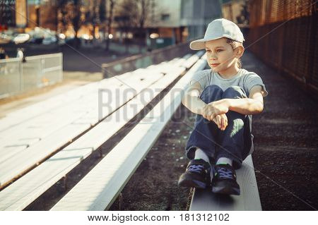 Pensive boy on a bench in the stadium. cute preteen looking at game on school field
