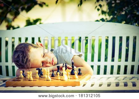 Tired boy fell asleep at the chessboard. child tired of playing chess