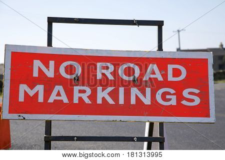 Red and white no road markings sign