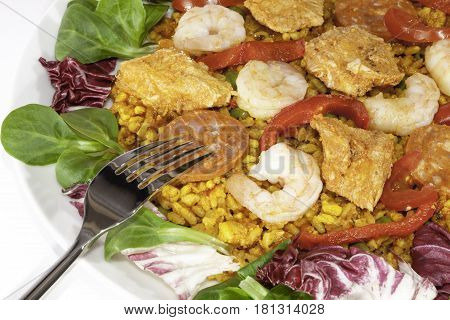 Paella with salad. Spanish meal of chicken chorizo and king prawn over short grain rice in a rich tomato sauce. Here served cold with salad leaves. Close up with fork.