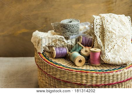 Woven rattan crafts and sewing supply box wooden spools rolls of lace aged wood background hobby fashion concept close up
