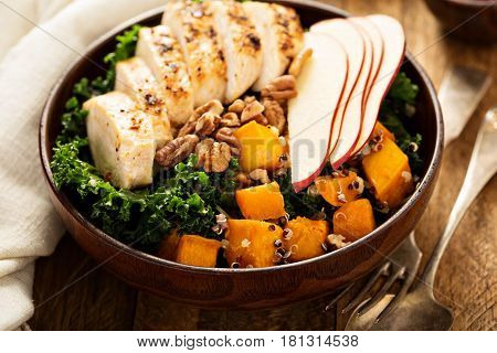 Healthy grain bowl with grilled chicken, quinoa, butternut squash, kale and apple