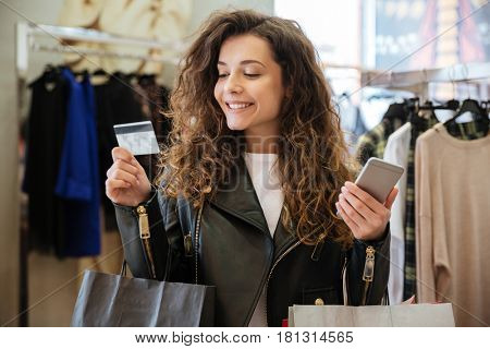 Photo of happy curly young lady standing in women's clothing shop with shopping bags holding debit card. Looking aside and holding phone.