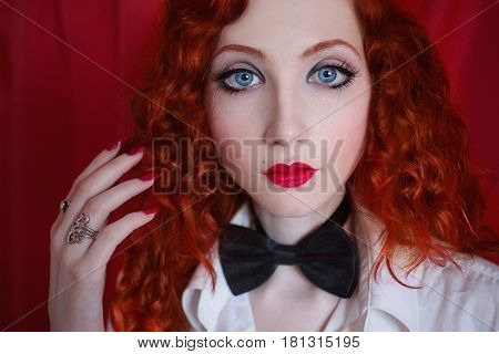 Portrait of a woman with long red curly hair in a white shirt and black bow tie on a red background. Red-haired girl with pale skin blue eyes a bright unusual appearance red lips and a sweet face.