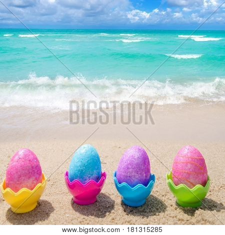 Easter color eggs on the sandy beach by the ocean - square photo Instagram format