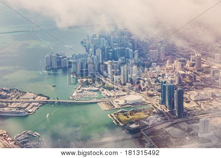 Aerial view of Miami from the aircraft. In the background of skyscrapers in the district of Wynwood. Fog over skyscrapers in Miami. Florida USA