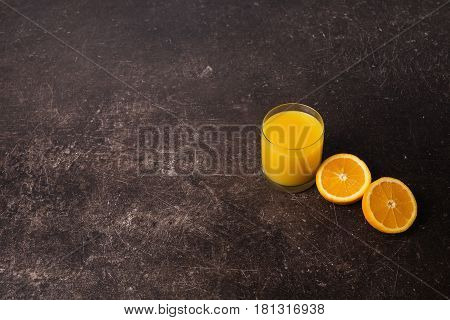 Freshly squeezed orange juice in a transparent glass. Cut an orange on a table.