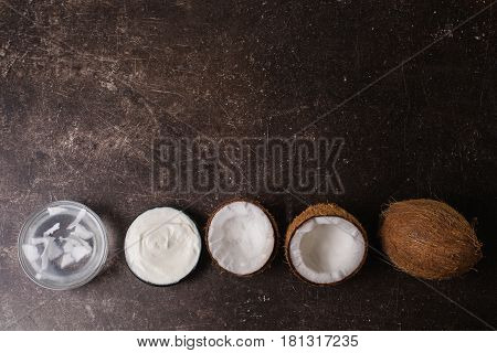 Coconut cream coconut milk and oil on a dark marble background. Exotic large walnut. Personal care. Spa treatments. Object on a dark background. Transparent object. Conceptual object. The objects are on the table. The object is on marble. The object lies