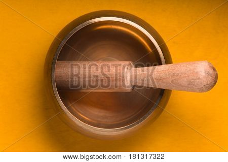 Metal bowl with a wooden stick on a yellow table horizontal